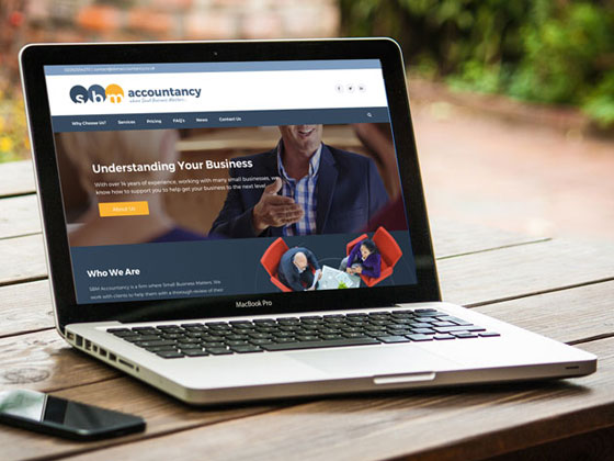 SBM Accountancy website homepage on a laptop on a wooden bench
