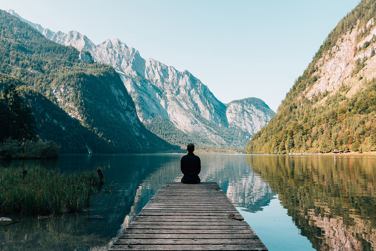 A man sitting at the end of a jetty surrounded by mountains and an alpine lake