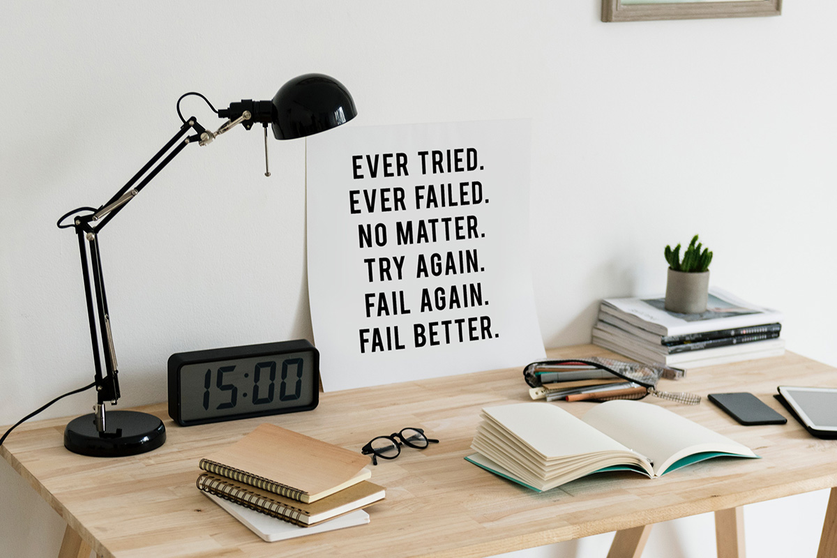 A poster on a desk that reads 'Ever tried. Ever failed. No matter. Try again. Fail again. Fail better'