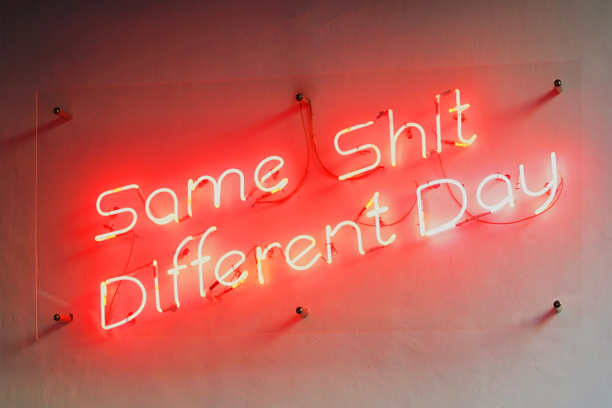 A neon sign that reads 'Same Shit Different Day'