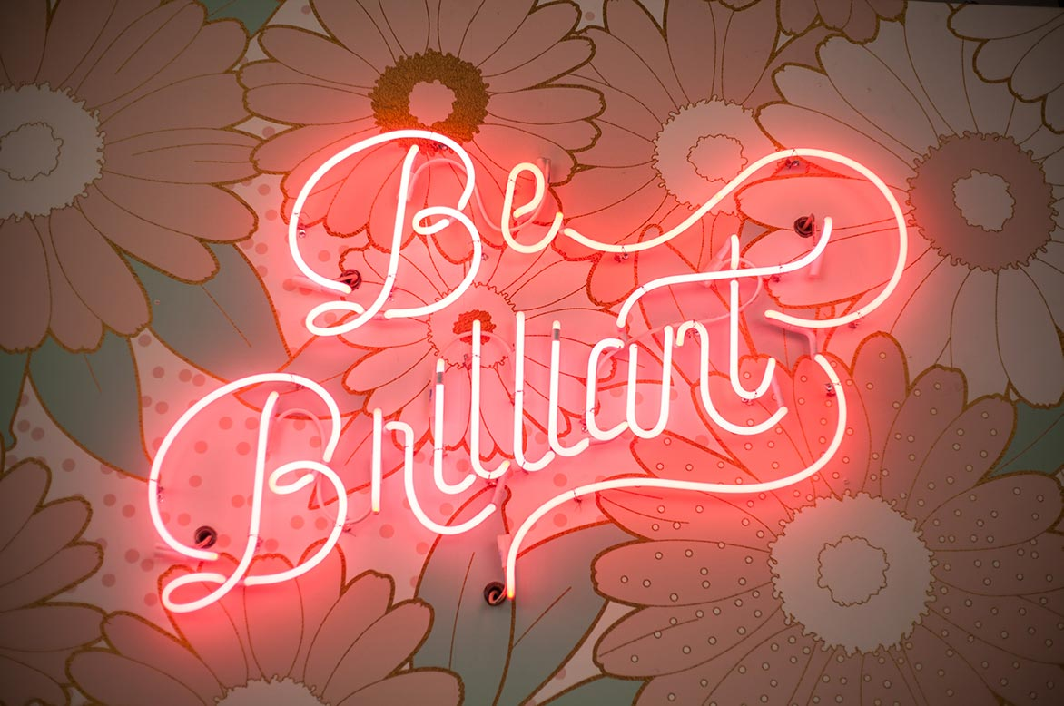 A neon sign on a floral wall that reads 'Be Brilliant'