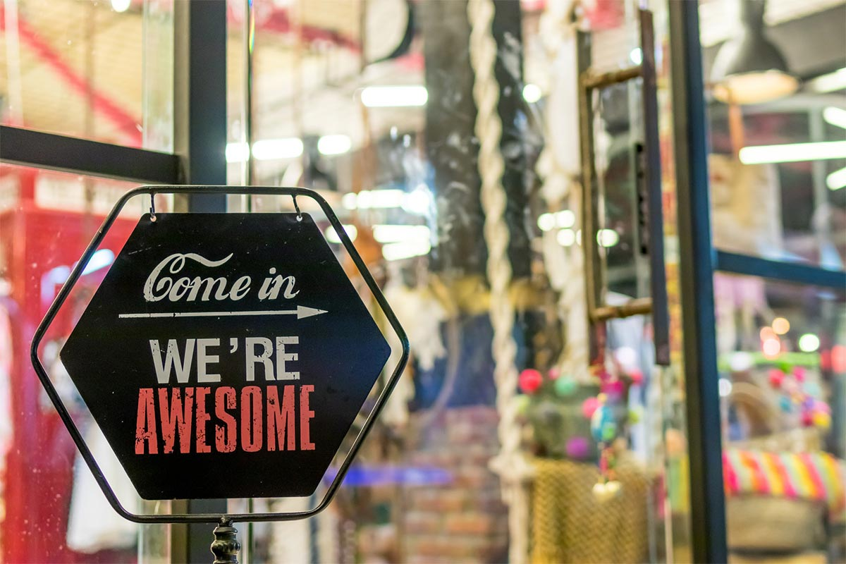 A street sign that reads 'come in, we're awesome'